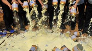 Des membres du Bureau local de surveillance de la qualité, vidant des boîtes de lait en poudre contaminé, à Shenzhen, le 19 septembre 2008.