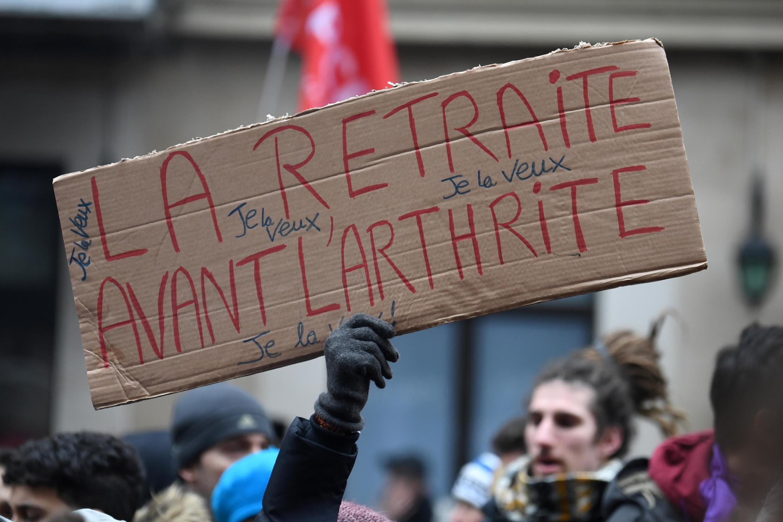 """Manifestante com cartaz: """"Quero a reforma antes da artrite"""". Paris, 5 de Dezembro de 2019."""