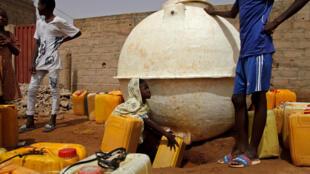 Un enfant récupère de l'eau dans une citerne de Kiffa.
