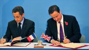 L'ex-président français Nicolas Sarkozy et l'ex-Premier ministre britannique David Cameron signent des traités lors du sommet Royaume-Uni-France à Lancaster House, à Londres en 2010.