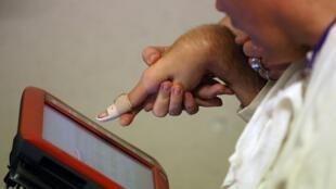 Rom Houben utilise un ordinateur pour communiquer avec ses proches.