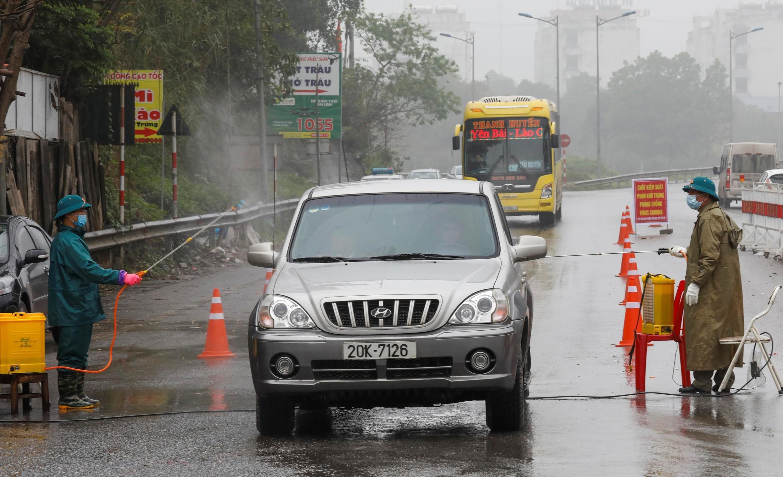 Đội chống dịch virus corona phun thuốc khử trùng vào xe trên một con đường ở tỉnh Thái Nguyên. Ảnh chụp ngày 07/02/2020.
