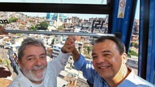 Le président brésilien Lula (g) avec le gouverneur de Rio de Janeiro Sergio Cabral lors de l'inauguration d'un téléphérique au complexo do Alemao, le 21 décembre 2010.