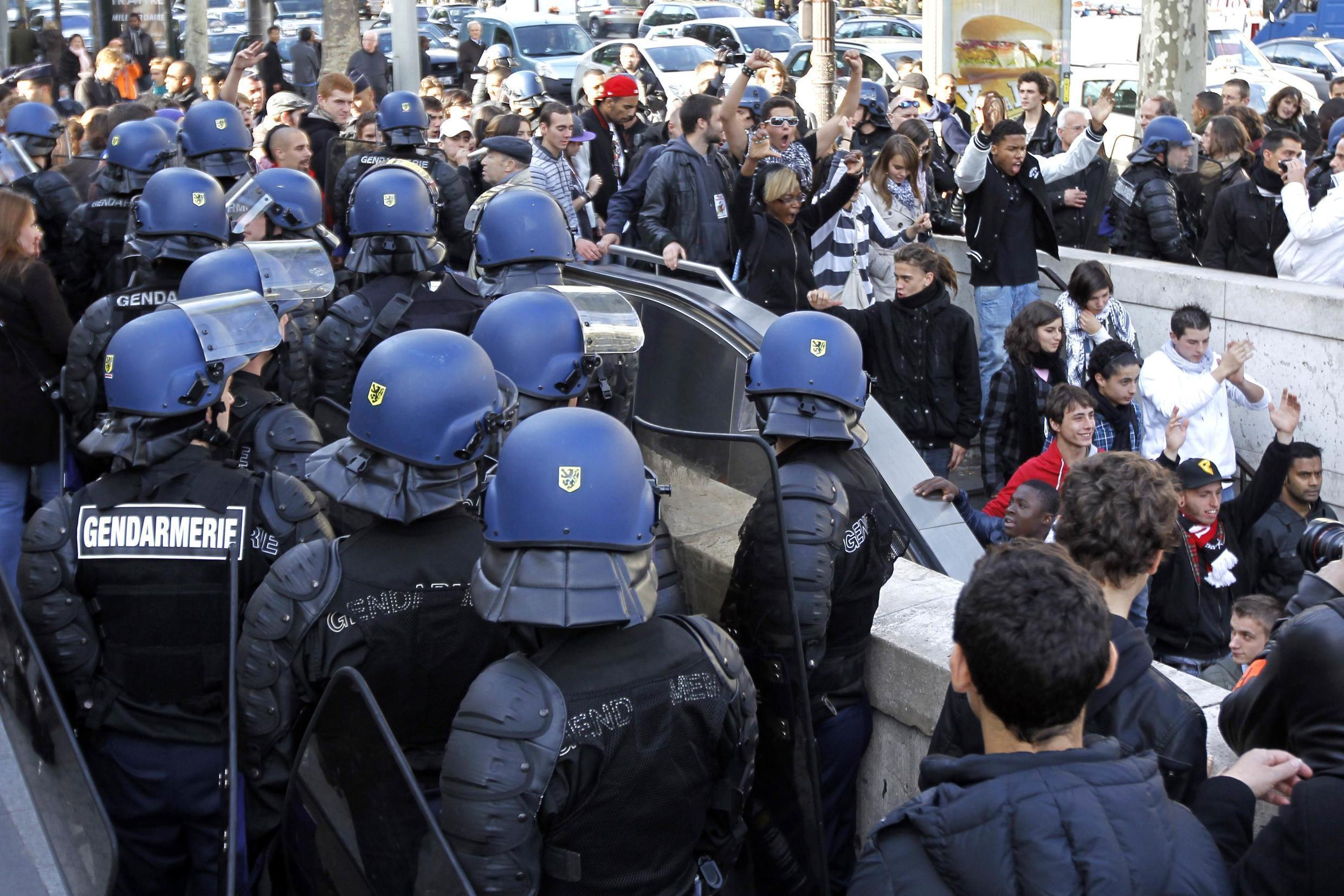 Police clear school students from Paris's Champs Elysées after a demonstration
