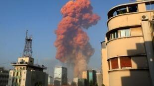 Un épais panache de fumée orangé s'élève depuis le port de Beyrouth, en fin d'après-midi, le 4 août 2020, après l'explosion d'un entrepôt contenant du nitrate d'ammonium.
