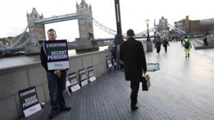 Imagem desta quarta-feira mostra manifestante em frente à prefeitura de Londres. Professores, trabalhadores da saúde e guardas da fronteira estão entre as categorias que deverão fazer a primeira greve massiva do Reino Unido, após 30 anos.