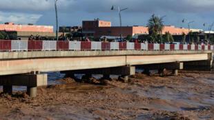 Des passants traversent un pont sur une rivière en crue à Aït Melloul, dans la région d'Agadir, le 29 novembre.