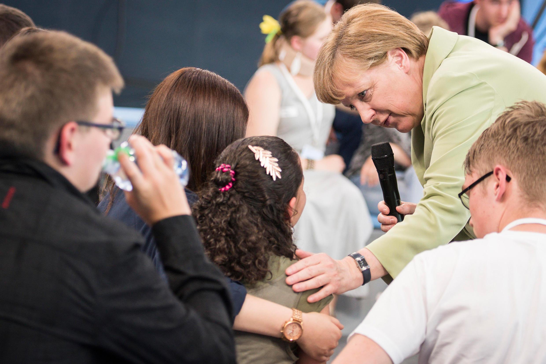 15 июля. Росток. Ангела Меркель успокаивает палестинскую девочку.