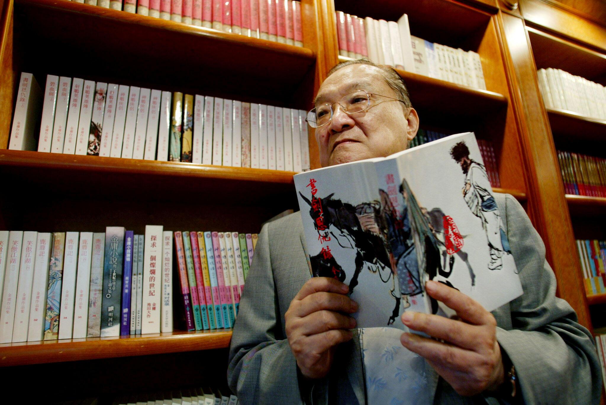 """Nhà văn Kim Dung tại văn phòng của ông ở Hồng Kông. Trên tay ông là tác phẩm đầu tay """"Thư kiếm ân cừu lục"""" ông viết năm 1955. Ảnh chụp ngày 29/07/2002."""