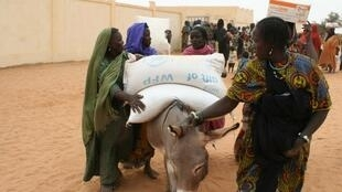 Des femmes repartent avec une aide alimentaire de la part du PAM, dans la région à Gourma Rharous, au Mali