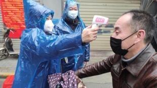 Mmoja wa wafanyakaziwa mji wa Wuhan, akifanyiwa vipimo vya joto katika hali ya kupambana dhidi ya ugonjwa wa Corona, Februari 1, 2020.