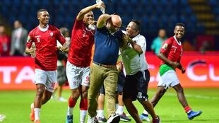 Madagascar's forward Faneva Andriatsima (2L) pours water on Madagascar's coach Nicolas Dupuis (C) as they celebrate winning the 2019 Africa Cup of Nations (CAN) Group B football match between Madagascar and Nigeria at the Alexandria Stadium on June 30, 201