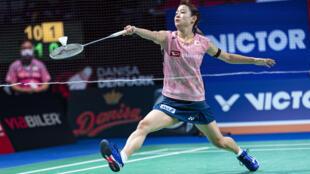 Striding forward: Nozomi Okuhara returns the shuttlecock to Michelle Li