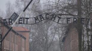 """A entrada do campo de Auschwitz  com a inscrição irônica """"Arbeit macht frei"""" (o trabalho liberta)."""