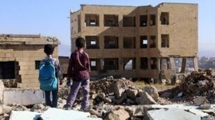 Estudiantes yemenitas frente a una escuela destruida por un bombardeo en la ciudad Taez, 16 de marzo 2017