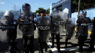 Un grupo de policía desaloja a  periodistas que se encontraban en la entrada de la jefatura policial en Managuas. 15 de diciembre de 2018.