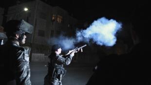 Un gendarme jordanien lance une bombre lacrymogène contre des manifestants qui protestent contre la hausse des prix  du combustible, le 15 novembre à Amman.