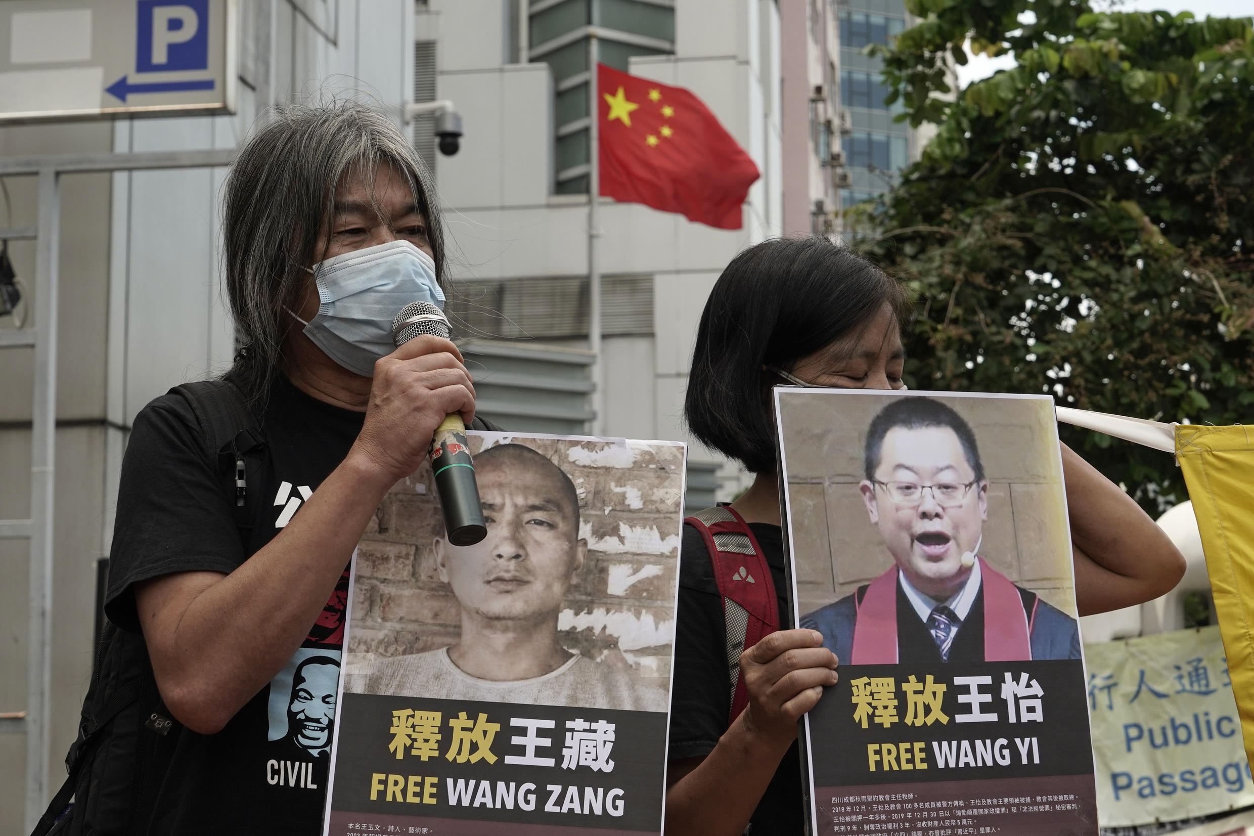 ro-democracy activists holding picture of detained Chinese human rights activists, protest outside the Chinese liaison office in Hong Kong, Thursday, Oct. 1, 2020 on the occasion of the China's National Day. They demanded to release the 12 Hong Kong activists detained at sea by Chinese authorities.
