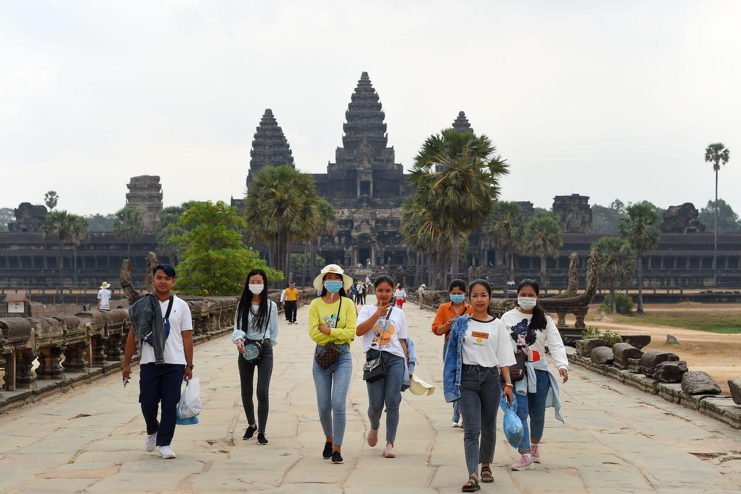 AFP Photo - People wear face masks as they visit Angkor Wat in Siem Reap province of Cambodia