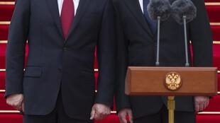 O presidente Vladimir Putin (à esq.) durante a cerimônia de posse ao lado de Dmitri Medvedev.