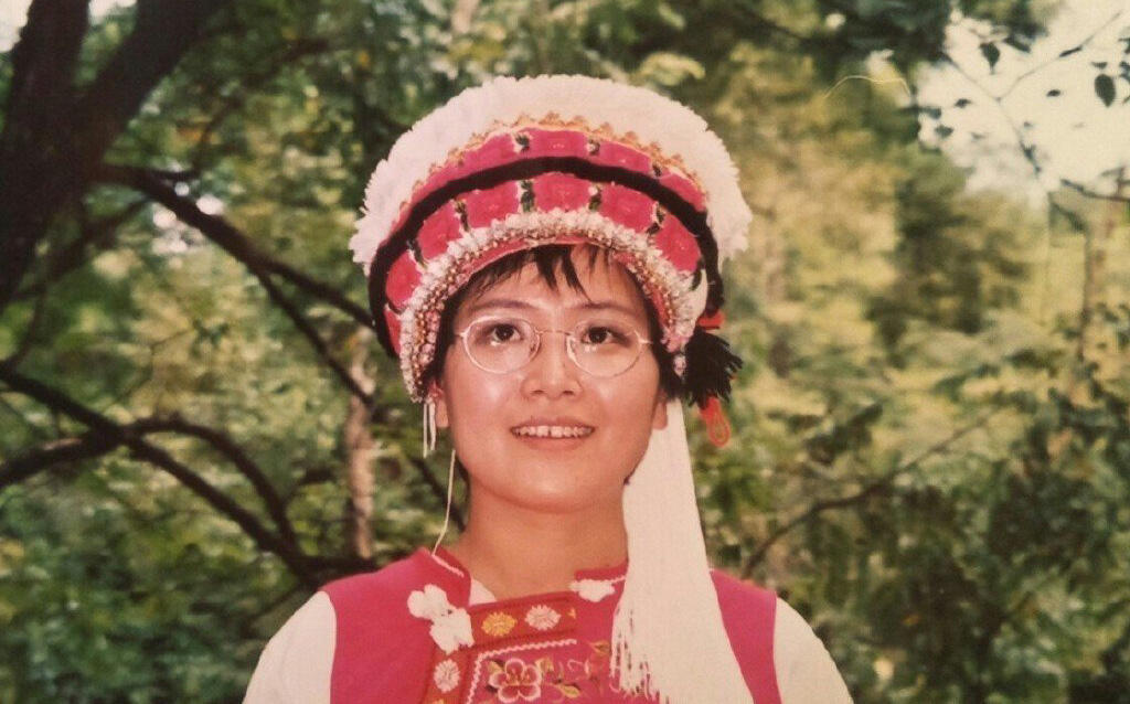 Feng Xiaoyan in happier times, picture taken when she was in her thirties, travelling through China and wearing a traditional minority dress.