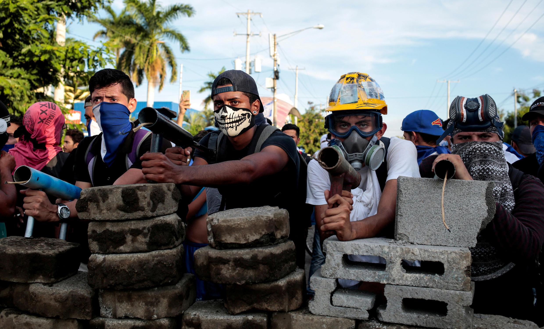 Des manifestants anti-Ortega tiennent une barricade lors d'affrontements avec la police anti-émeute à Managua, le 30 mai.
