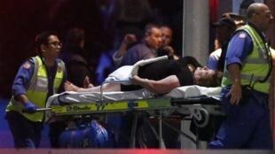 Спасатели выносят из кафе в Сиднее раненую женщину