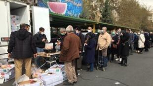 Une longue file d'attente se forme sur le marché de marché de Qezel Qaleh à Téhéran, où les gens font la queue pour acheter du poulet.