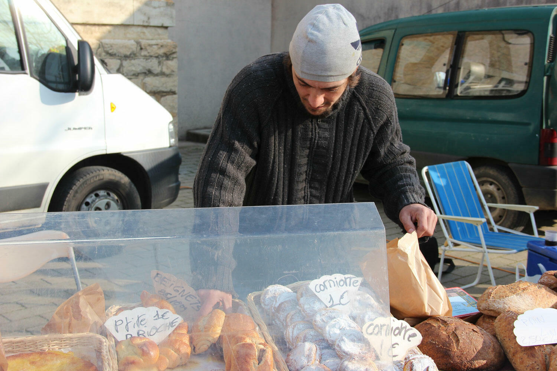 Romain Ménaboeuf arrange ses pains derrière son stand du marché de Bletterans, dans la Bresse jurassienne.
