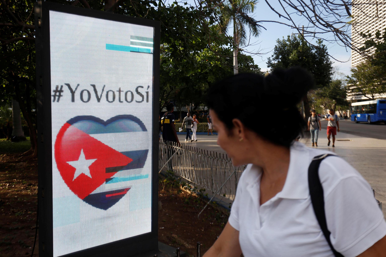 """Женщина проходит мимо плаката с надписью """"Я голосую за!"""""""