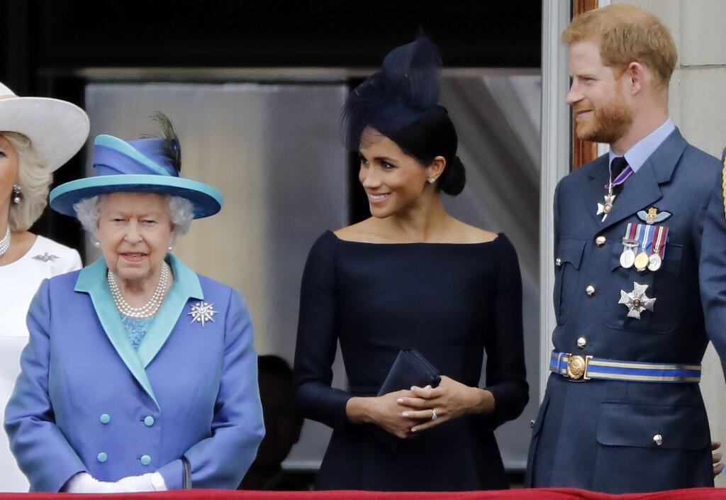 La reine Élisabeth II, Meghan et le prince Harry se tiennent sur le balcon du palais de Buckingham à Londres, le 10 juillet 2018.