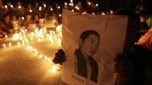 Một em bé cầm  bức chân dung tu sĩ Tây Tạng  đã tự thiêu, Phuntsog , trong  buổi lễ tưởng niệm tại  trung tâm tỵ nạn Lalitpur, ngày 11/10/2011