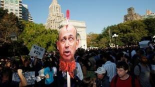 """紐約華盛頓廣場示""""佔領華爾街運動""""示威者舉着高盛集團首席執行官勞埃德•布蘭克費恩的頭像2011年10月8"""