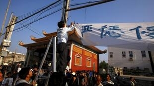 與政府達成協議之後的烏坎村民拆下橫幅標語,2011年12月21日。