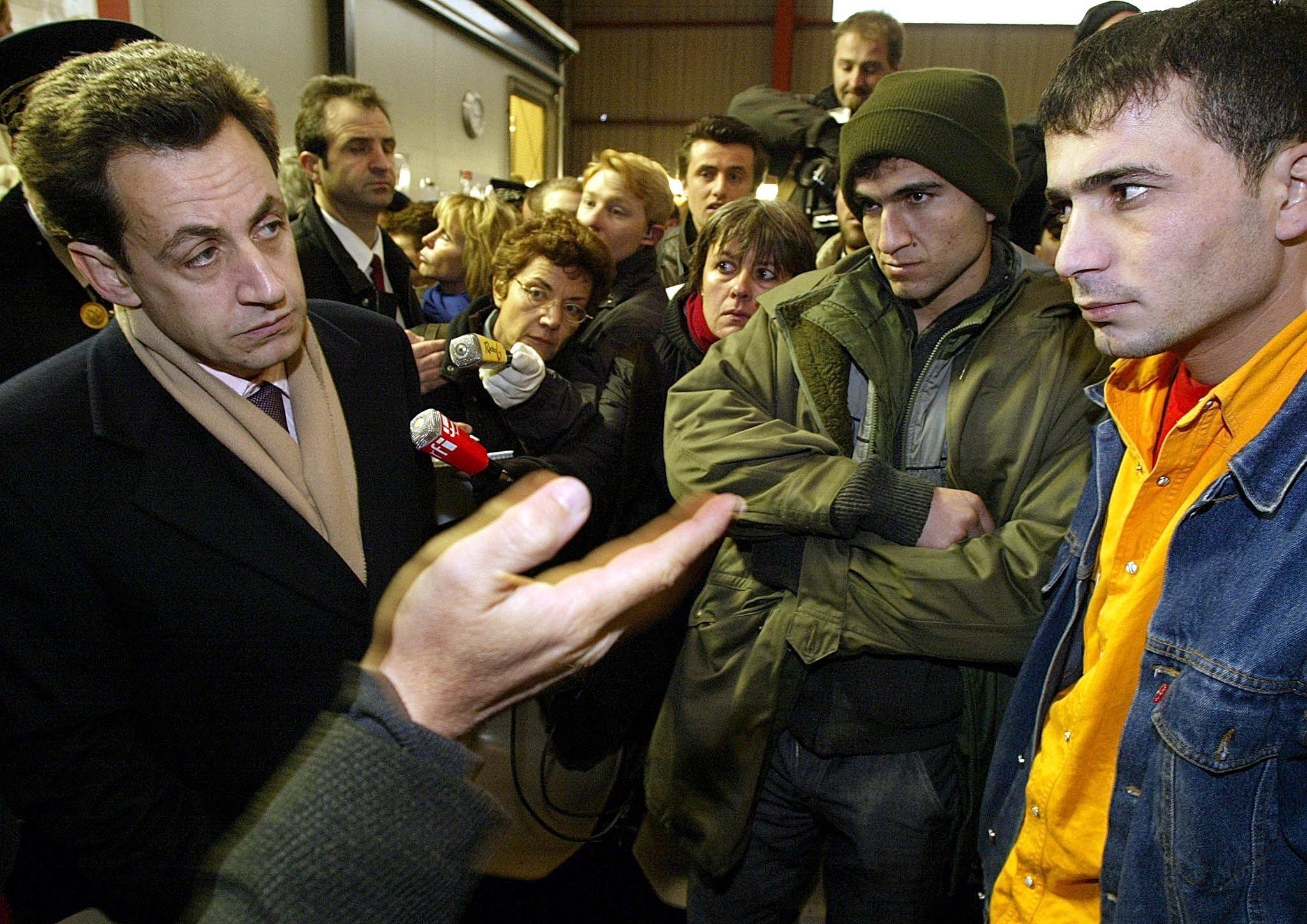 10 December 2002 - French Interior Minister Nicolas Sarkozy speaks with some of the last refugees of the Sangatte Red Cross centre