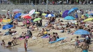 People sunbathe on Bogatell beach in Barcelona. Some local residents have protested, saying there are too many tourists.