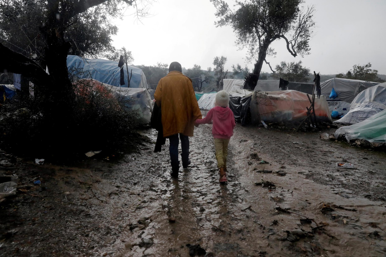 Des réfugiés traversent le camp de Moria, sur l'île de Lesbos en Grèce, le 13 décembre 2019.