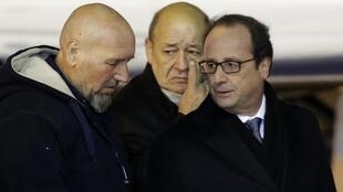 Serge Lazarevic (L) with French Defence Minister Jean-Yves Le Drian and President François Hollande at Villacoublay airport
