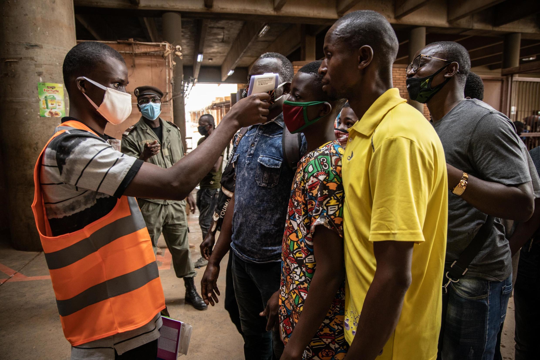 Un agent de la mairie prend la température des personnes à l'entrée du marché Rood Woko à Ouagadougou. Le 25 mars 2020.