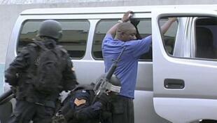 La policía cachea a un hombre delante de su camioneta en Kingston, Jamaica, el 24 de mayo de 2010.