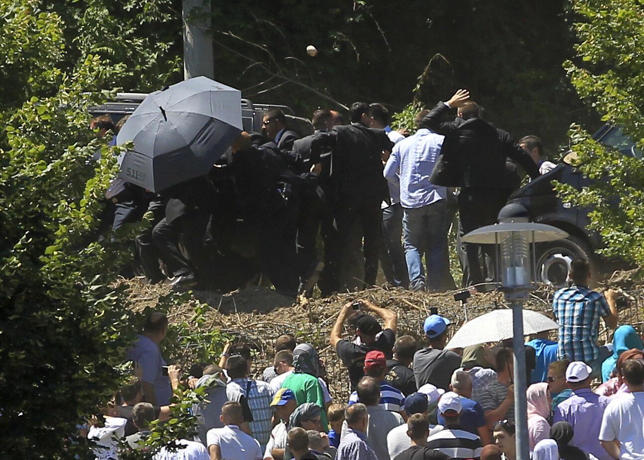 Телохранители закрывают зонтом премьер-министра Сербии Александра Вучича, в сторону которого из толпы летят камни, Сребреница, 11 июля 2015 г.