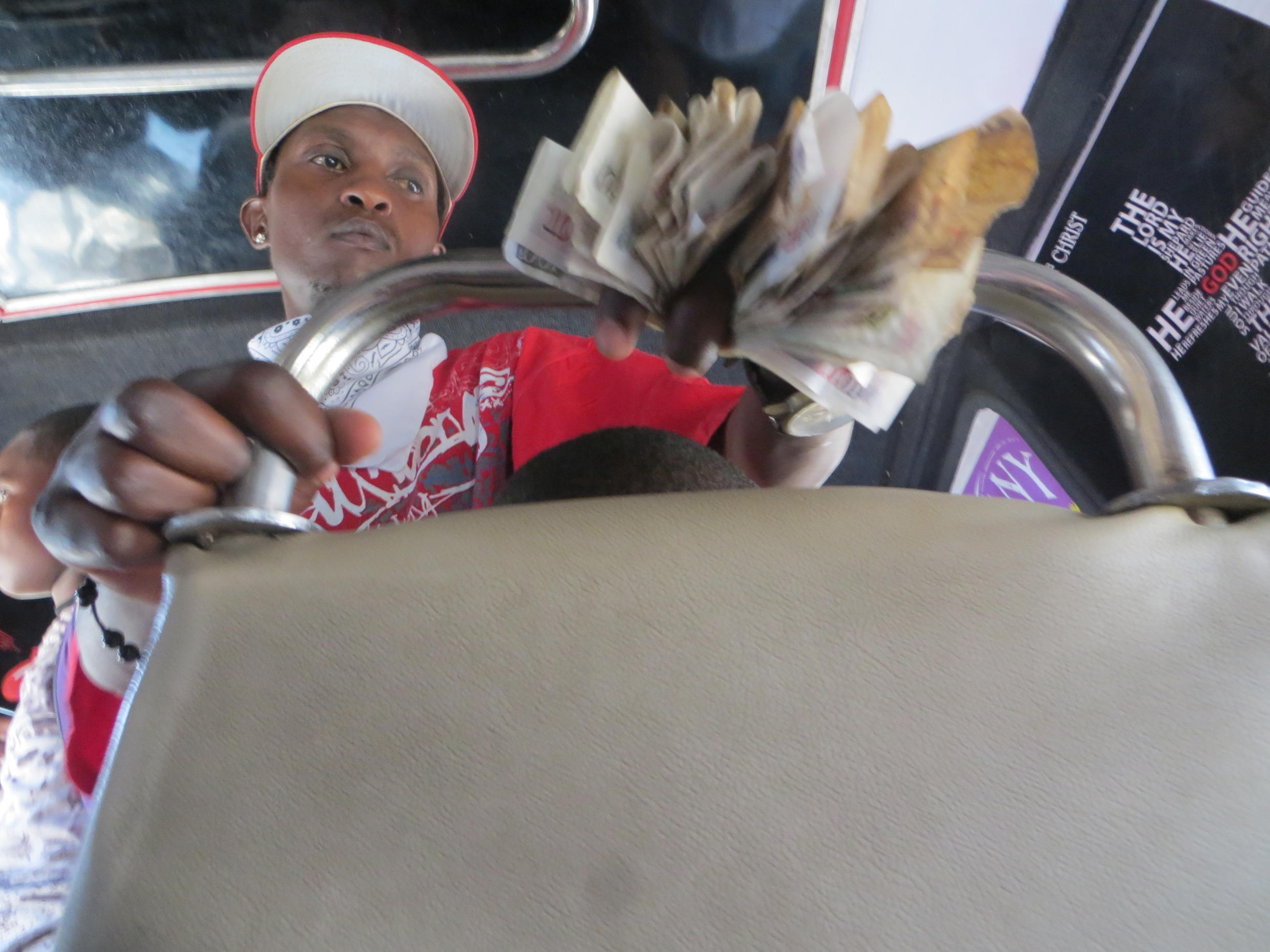 A makanga collects money from passengers on one of Nairobi's matatus. Many of those working in Kenya's matatu industry are skeptical about switching from cash to an electrionic card.
