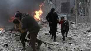 Syrian civilians run for cover after a bomb hits Eastern Ghouta in the suburbs of Damascus.