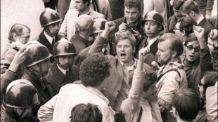 """Daniel Cohn-Bendit (centro) canta o hino socialista """"A International"""", em 6 de maio de 1968 em Paris, cercado pelos policiais e outros estudantes protestantes, antes de ir ao Comitê Disciplinar da Universidade de Paris Sorbonne."""