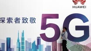 (Ảnh minh họa) - Một người đàn ông nói chuyện trên điện thoại di động, bên cạnh biển quảng cáo công nghệ 5G của Hoa Vi, tại triển lãm PT Expo ở Bắc Kinh, Trung Quốc, ngày 26 tháng 09 năm 2018.