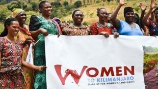 Wanawake wakishikikilia bango la kuhamasisha wanawake kupanda mlima wa Kilimanjaro kama ishara ya kupambana na mifumo kandamizi kwenye jamii zetu.