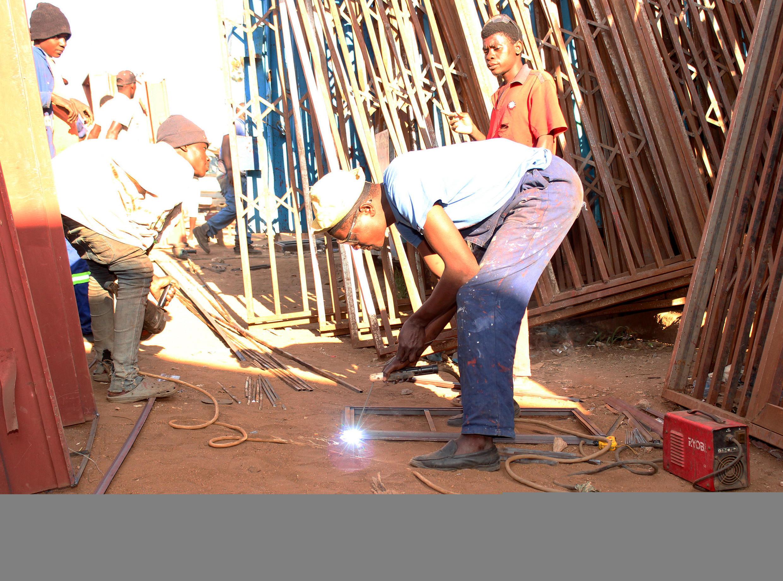 Gift Kamkwamba makes metal windowframes at his shop in Blantyre, Malawi, while workers look on