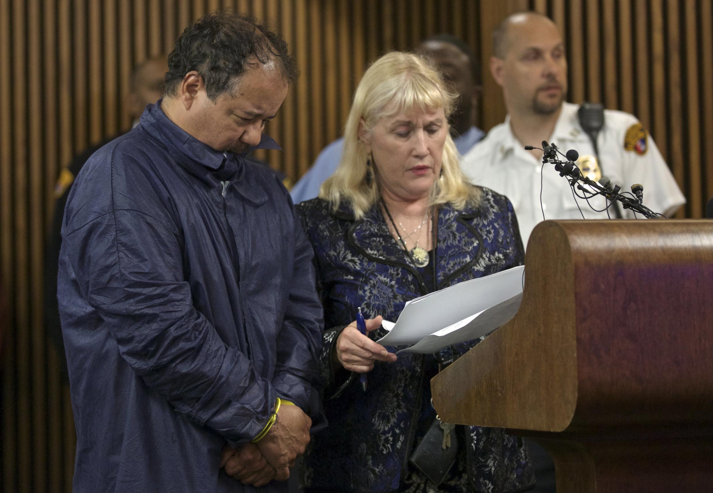 Ariel Castro (G) menotté accompagné de Kathleen DeMetz, une avocate commise d'office comparaît devant un tribunal de la ville, le 9 mai 2012