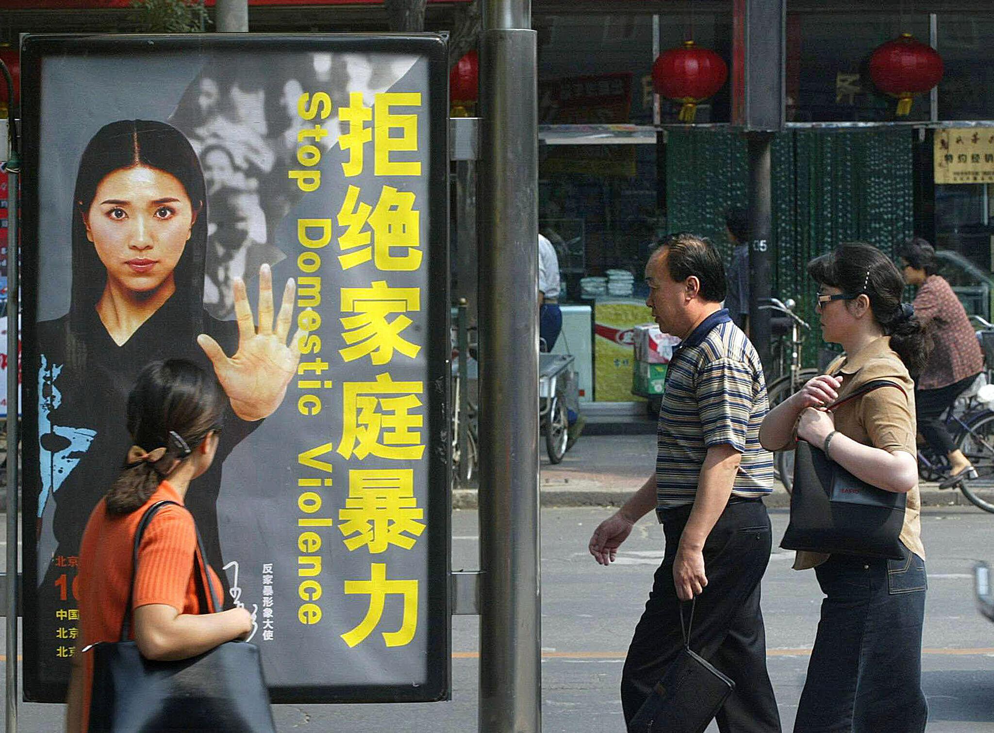 资料图片:北京街头反家庭暴力宣传海报。摄于2002年9月17日。