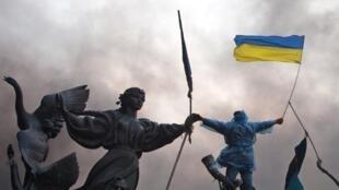 2014年2月20日,一名示威者在基輔市中心獨立廣場雕塑上揮舞烏克蘭國旗。